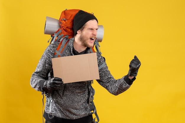 Freute sich männlicher tramper mit lederhandschuhen und rucksack mit leerem karton, der seine gefühle ausdrückte