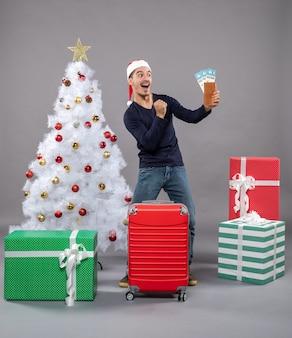Freute sich mann hielt seine reisetickets in der nähe von weihnachtsbaum auf grau