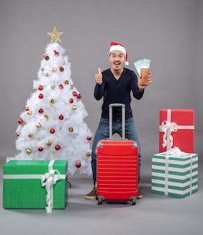 Freute sich mann mit rotem koffer, der seine reisetickets zeigt und daumen hoch zeichen auf grau macht