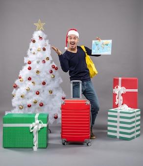 Freute sich weihnachtsmann mit weihnachtsmütze, der weltkarte auf grau hält