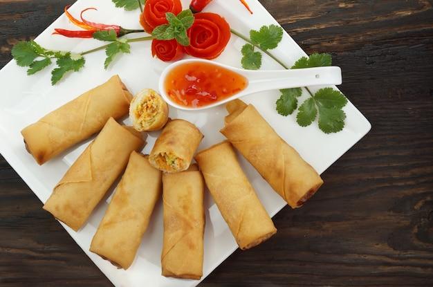 Fried chinese-frühlingsrollen dienten mit chili-sauce auf holz