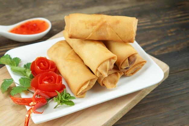 Fried chinese-frühlingsrollen dienten mit chili-sauce und verzierten rosafarbenen tomaten mit dem grün, das auf holz, raum leaved war. konzept asiatisches essen