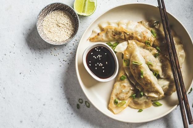Fried korean-mehlklöße mit frühlingszwiebel und soße auf weißer platte, draufsicht.