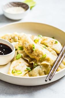 Fried korean-mehlklöße mit frühlingszwiebel und soße auf weißer platte.