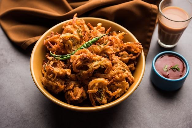 Fried onion pakora oder pyaj pakoda, auch bekannt als crispy kanda bhaji / bhajji / bajji, beliebter indischer snack zur teezeit während der regenzeit. serviert mit tomatenketchup