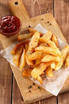 Fried potatoes auf altem hölzernem schneidebrett mit schüsselketschup.