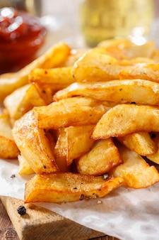 Fried potatoes auf altem hölzernem schneidebrett. nahansicht.