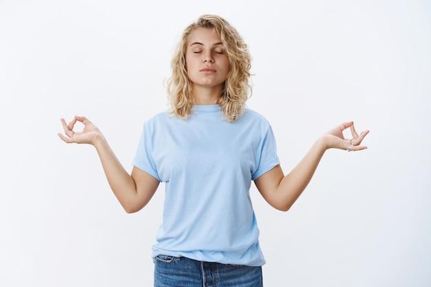 Frieden ist lebenswichtig. porträt einer ruhigen und entspannten, ungestörten jungen frau, die mit geschlossenen augen und fokussiertem gesicht in lotuspose meditiert, nirvana mit mudra-zeichen durchsuchen, yoga praktizieren