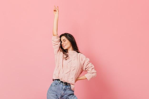 Friedensliebendes mädchen, das auf rosa hintergrund lächelt. frau im warmen outfit hebt ihre hand und zeigt friedenszeichen.