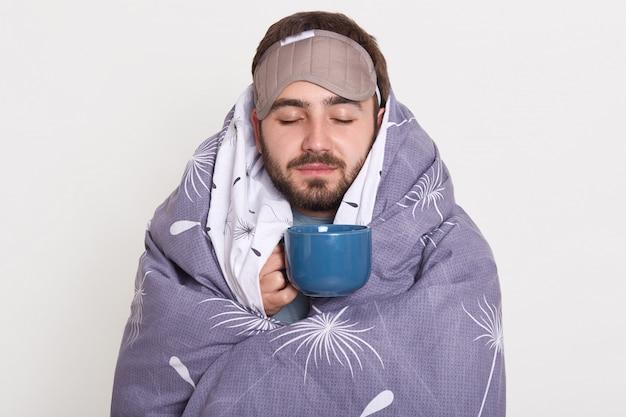 Friedlich ruhig schläfrig fröhlicher junger mann mit bart, bedeckt sich mit decke, schließt die augen, hält tasse mit kaffee