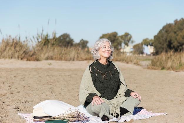 Friedliche ältere frau, die draußen meditiert