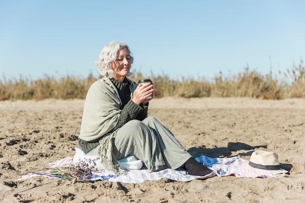 Friedliche ältere frau, die kaffee hält