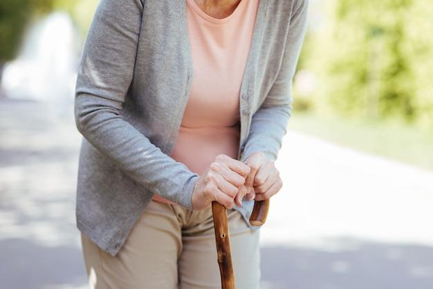 Friedliche alte frau im ruhestand, die den stock hält und sich darauf stützt, während sie im park geht