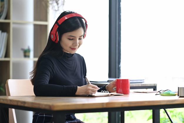 Friedliche asiatische frau, die kopfhörer trägt und ihr tagebuch schreibt.