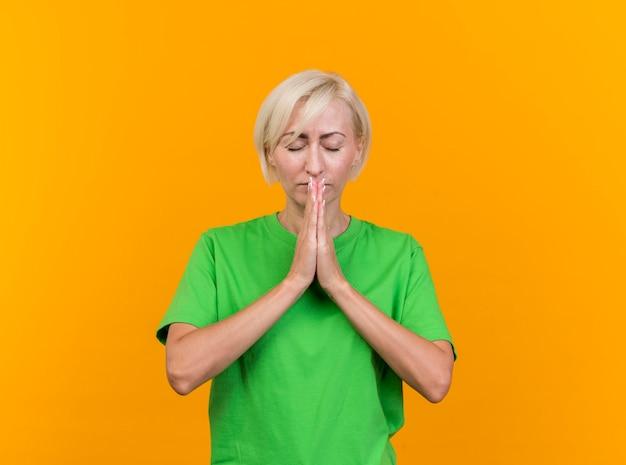Friedliche blonde slawische frau mittleren alters, die hände zusammenhält und mit geschlossenen augen betet, lokalisiert auf gelber wand mit kopienraum
