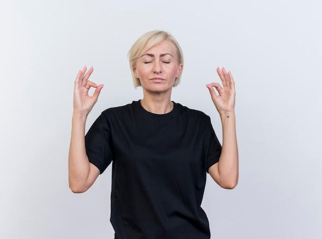 Friedliche blonde slawische frau mittleren alters, die mit geschlossenen augen meditiert, lokalisiert auf weißem hintergrund mit kopienraum