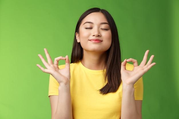 Friedliche, charmante asiatin brünett frische luft ein, entspannt glückliches atmen, schließen die augen lächelnd, halten die hände zen-mudra-zeichen erreichen nirvana, meditation, yoga, grüner hintergrund.