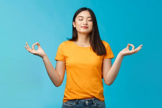 Friedliche, charmante, entspannte asiatische mädchen, buddhistische meditation, atmung, frische luft einatmen, yoga einatmen, enge augen lächeln erleichtert, lotus-nirvana-pose stehen, zen erreichen, blauer hintergrund stehen.