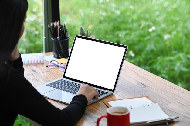 Friedliche designerin, die mit laptop-computer im büro arbeitet.
