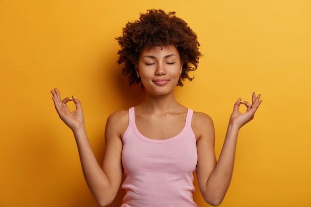 Friedliche dunkelhäutige frau mit afro-frisur trägt rosiges trägershirt