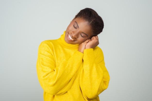 Friedliche frau, die gelben pullover genießt