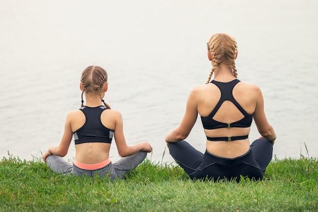 Friedliche frau und ihre kleine tochter sitzen in der nähe des sees und praktizieren gemeinsam yoga auf grünem gras.