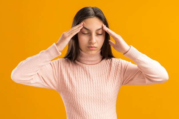 Friedliche hübsche teenager-mädchen hebt augenbrauen mit geschlossenen augen isoliert auf orangefarbener wand