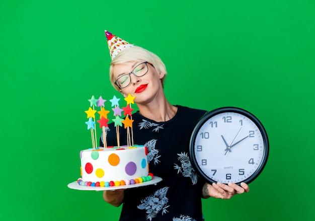 Friedliche junge blonde partygirl, die brille und geburtstagskappe hält, die geburtstagstorte und uhr mit geschlossenen augen lokalisiert auf grünem hintergrund mit kopienraum hält
