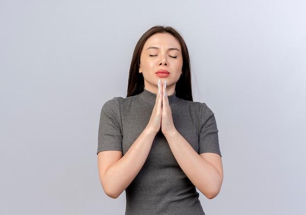 Friedliche junge hübsche frau, die hände in gebetsgeste setzt, die mit geschlossenen augen betet, lokalisiert auf weißem hintergrund mit kopienraum