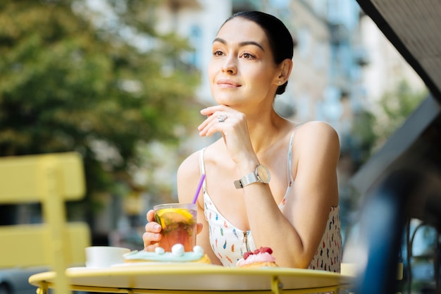 Friedliche stimmung. entspannte junge frau, die niedlich und lächelnd schaut, während sie am kleinen tisch mit einem glas frischer limonade in ihrer hand sitzt
