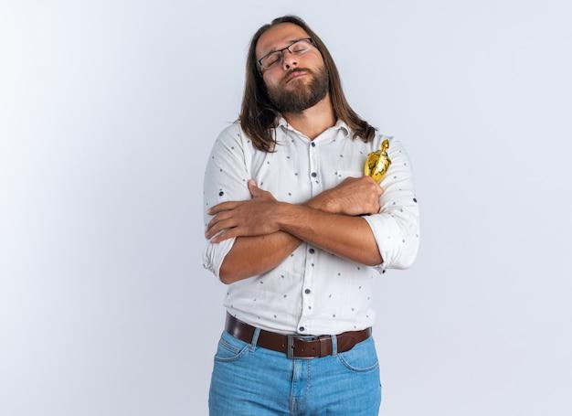 Friedlicher erwachsener gutaussehender mann mit brille, der siegerpokal hält und die hände mit geschlossenen augen gekreuzt hält, isoliert auf weißer wand mit kopierraum