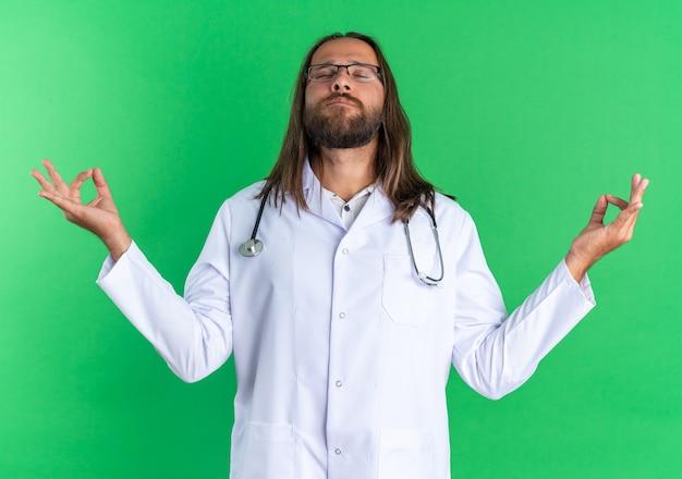 Friedlicher erwachsener männlicher arzt mit medizinischem gewand und stethoskop mit brille, der mit geschlossenen augen meditiert, isoliert auf grüner wand