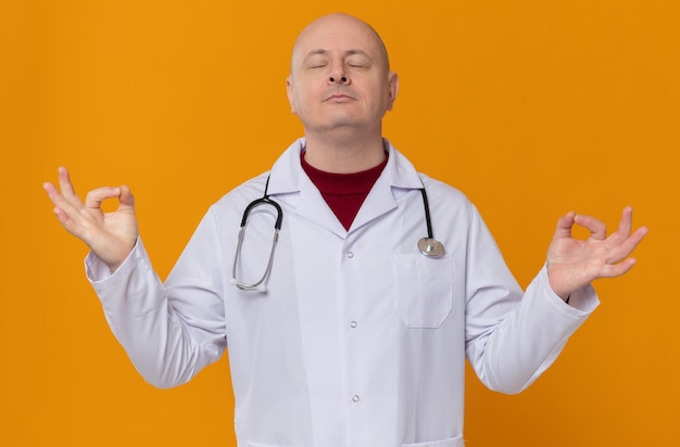 Friedlicher erwachsener mann in arztuniform mit stethoskop meditierend im stehen mit geschlossenen augen