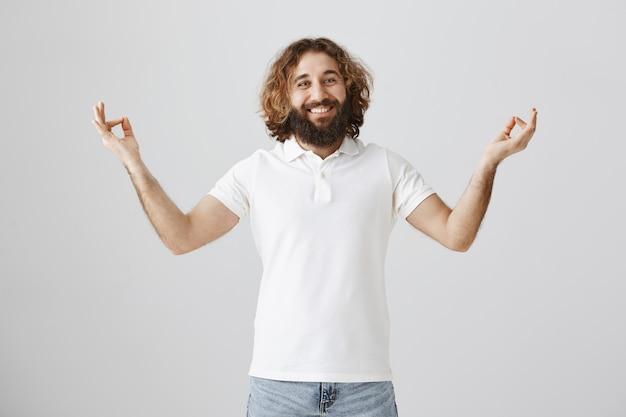 Friedlicher glücklicher nahöstlicher mann, der während der meditation lächelt