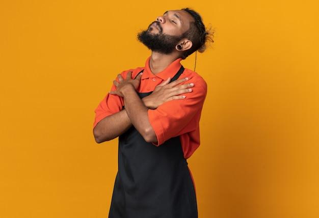 Friedlicher junger afroamerikanischer männlicher barbier in uniform, der die hände auf den schultern mit geschlossenen augen gekreuzt hält, isoliert auf oranger wand mit kopierraum