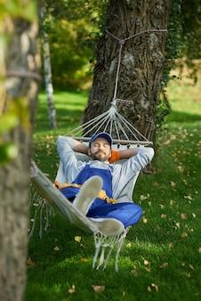 Friedlicher junger arbeiter in uniform, der eine pause macht und an einem sonnigen tag in einer hängematte im freien mit geschlossenen augen liegt