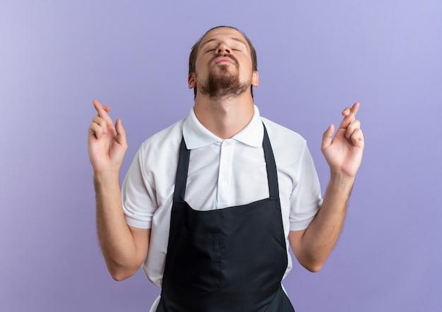 Friedlicher junger hübscher friseur, der uniform trägt, die gekreuzte finger tut und mit geschlossenen augen wünscht, die auf lila hintergrund lokalisiert werden