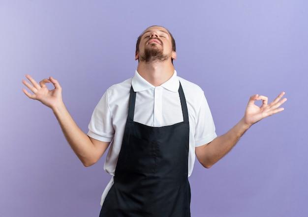 Friedlicher junger hübscher friseur, der uniform trägt, die ok zeichen mit geschlossenen augen lokalisiert auf purpurrotem hintergrund tut