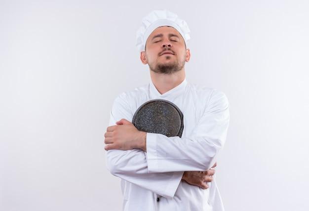 Friedlicher junger hübscher koch in der kochuniform, die bratpfanne mit geschlossenen augen auf lokalisiertem weißen raum hält