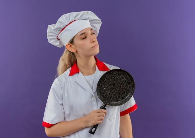 Friedlicher junger hübscher koch in der kochuniform, die bratpfanne mit geschlossenen augen lokalisiert auf lila raum hält