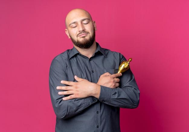 Friedlicher junger kahlköpfiger callcenter-mann, der hände auf der brust gekreuzt hält und siegerpokal mit geschlossenen augen hält, die auf purpurrotem hintergrund mit kopienraum lokalisiert werden