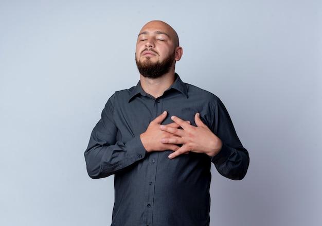 Friedlicher junger kahlköpfiger callcenter-mann, der hände auf sein herz mit geschlossenen augen lokalisiert auf weißem hintergrund mit kopienraum setzt