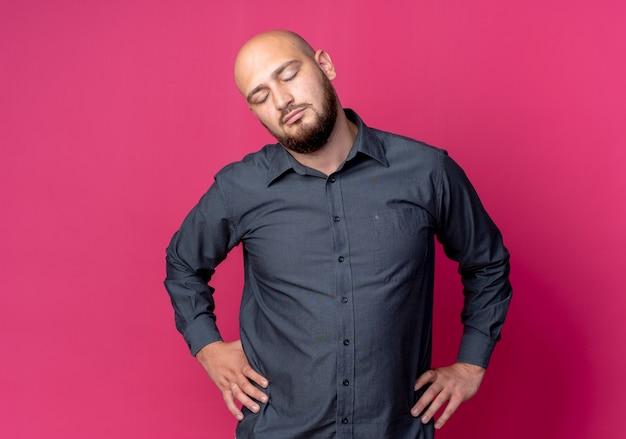 Friedlicher junger kahlköpfiger callcenter-mann, der hände auf taille mit geschlossenen augen lokalisiert auf purpurrotem hintergrund mit kopienraum setzt