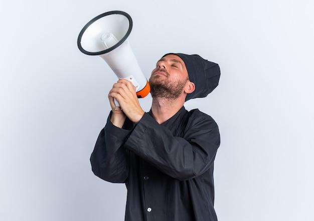 Friedlicher junger kaukasischer männlicher koch in kochuniform und mütze, der den lautsprecher mit nach hinten geneigtem kopf mit geschlossenen augen isoliert auf weißer wand mit kopierraum hält