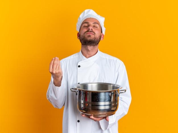 Friedlicher junger kaukasischer männlicher koch in kochuniform und mütze mit topf geben vor, etwas mit nach hinten geneigtem kopf mit geschlossenen augen isoliert auf oranger wand zu halten
