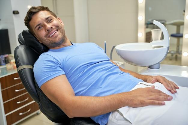 Friedlicher junger mann, der sich positiv über die zahnärztliche untersuchung fühlt