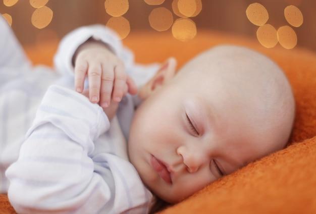 Friedlicher kleiner junge, der auf einem bett liegt, während er schläft