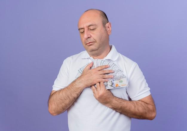 Friedlicher lässiger reifer geschäftsmann, der geld mit geschlossenen augen lokalisiert auf purpurrotem hintergrund mit kopienraum hält