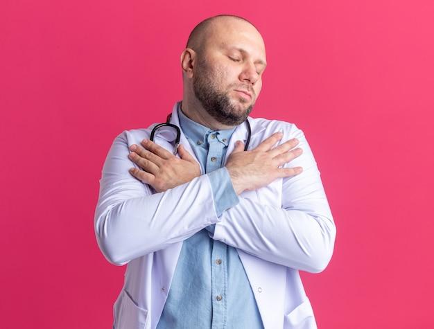 Friedlicher männlicher arzt mittleren alters, der ein medizinisches gewand und ein stethoskop trägt und die hände auf den schultern mit geschlossenen augen isoliert auf rosa wand hält
