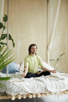 Friedlicher mann, der im bett sitzt und morgenmeditation tut, yogalehrer im modernen designhaus mit grünen pflanzen, die yoga praktizieren